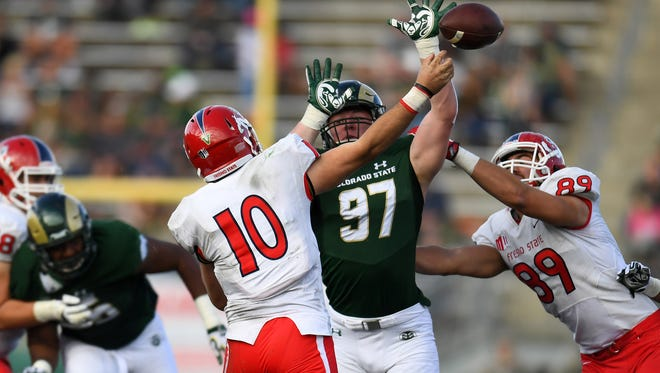 CSU defensive lineman Toby McBride, one of seven freshmen in the Rams' defensive playing rotation, pressures Fresno State quarterback Zach Cline as he throws during a Nov. 5 game at Hughes Stadium. CSU won the game 37-0 for its first shutout since 1997.