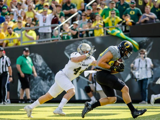 Oregon tight end Johnny Mundt scores a touchdown on a pass reception during the second quarter as UC Davis defensive back Zach Jones (44) follows, during an NCAA college football game in Eugene, Ore., Saturday, Sept. 3, 2016.