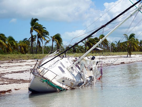 A capsized sailboat boat sits in the water off Key West following the passage of 2017's Hurricane Irma. County officials in the Florida Keys are planning to raise the level of some area roads to serve as flood barriers in anticipation of worsening storms.