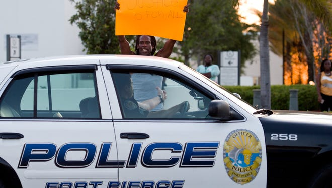 """Lonnie Melvin, of Fort Pierce, who stands outside the chambers during a Fort Pierce City Hall during an April protest, said the community needs justice for the fatal police shooting of 21-year-old Demarcus Semer. """"I didn't know this young man, but he lived right around the corner from me, and I heard good things about him, """" he said. """"We need justice."""" (FILE PHOTO)"""