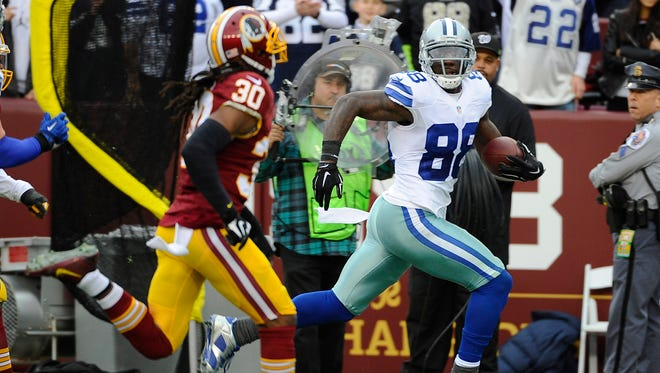 Dec 28, 2014; Landover, MD, USA; Dallas Cowboys wide receiver Dez Bryant (88) scores a touchdown on a 65 yard reception as Washington Redskins free safety E.J. Biggers (30) chases during the first half at FedEx Field.
