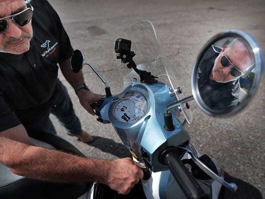 Andy Nix, director of My City Rides, pulls his scooter
