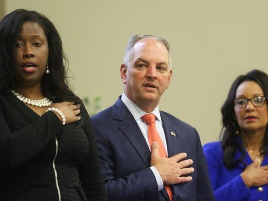 Gov. John Bel Edwards, center, stands for the national