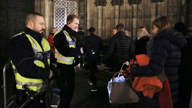 Police officers inspect people's bags at the entrance of the Cologne Cathedral in Cologne, Germany, on Dec. 24, 2016. Christmas services took place at the cathedral under police protection.