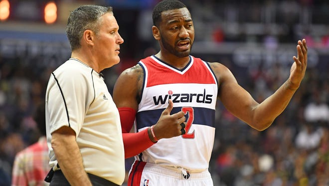 Washington Wizards guard John Wall (2) talks with referee Monty McCutchen (13) against the Brooklyn Nets during the second half at Verizon Center.