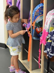 Ema Kamada goes to her cubby for some supplies on Sept. 12 at the Novi Early Childhood Education Center.