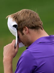 Sam Burns covers his face after hitting a bogey on