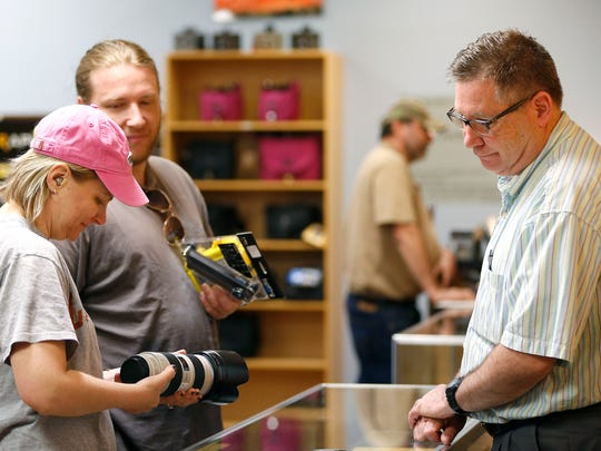 Lawrence Photo & Video sales associate Jim Wygant helps Stefanie Zimmerhakl as she looks at a camera lens on Wednesday, April 8, 2015. The store is closing after almost 42 year in business.