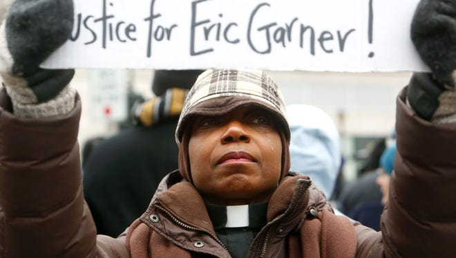 Betty Tom, pastor of First Presbyterian Church in Mount Vernon, N.Y., sheds a tear while participating in a Dec. 5 demonstration in White Plains, N.Y., against grand jury decisions not to indict police officers involved in the chokehold death of Eric Garner in New York City and the fatal shooting of Michael Brown in Ferguson, Mo.