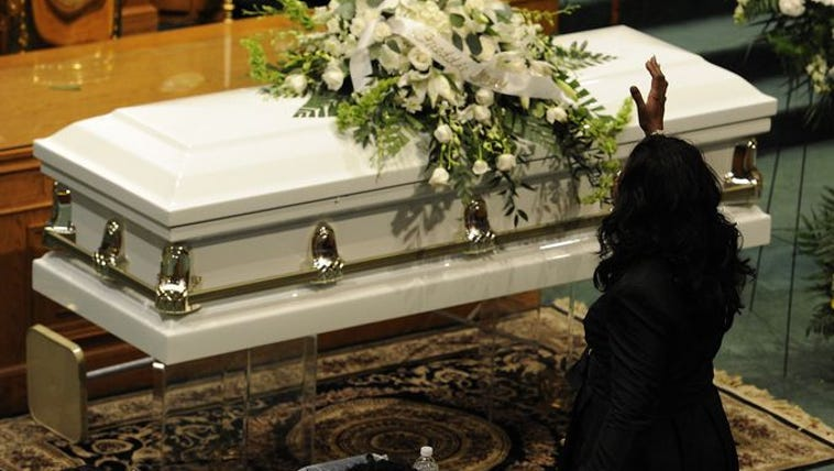 A woman gestures in front of the casket of Freddie