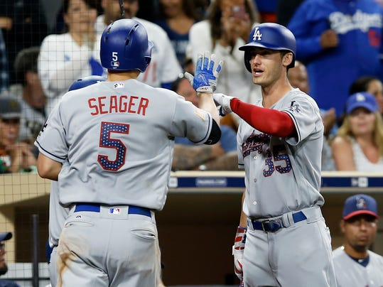Los Angeles Dodgers' Corey Seager, left, gets congratulations from Cody Bellinger after hitting a solo home run during the fifth inning of a baseball game against the San Diego Padres in San Diego, Saturday, July 1, 2017. (AP Photo/Alex Gallardo)