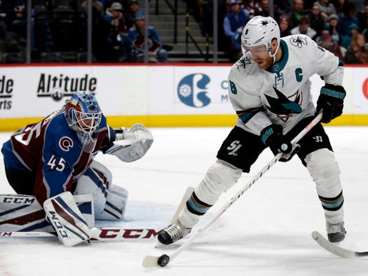 San Jose Sharks center Joe Pavelski (8) collects the puck in front of Colorado Avalanche goaltender Jonathan Bernier (45) in the second period of an NHL hockey game in Denver on Thursday, Jan. 18, 2018.(AP Photo/Joe Mahoney)