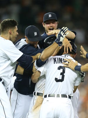 Detroit Tigers' Ian Kinsler celebrates with teammates after his bunt that scored the winning run on a throwing error against the Kansas City Royals on Friday, May 8,2015 at Comerica Park in Detroit.