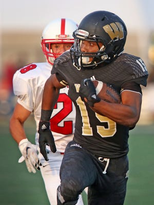 Warren Central's #15 Isaac Avant runs for a touchdown in first half action with Center Grove #28 Sam Bolin chasing in the Center Grove at Warren Central football game, Friday, August 21, 2015.