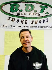 Curt Goure, owner of B.D.T Smoke Shops, poses on March