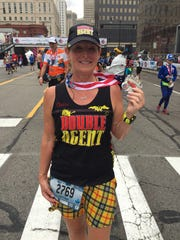 """Claire Gladstone, 50, of Ridgefield, Conn., shows off her """"Double Agent"""" jersey, which signifies that she's a member of an elite group -- people who've run, well, just say an astounding number of both marathons and half marathons, Sunday, October 15, 2017."""
