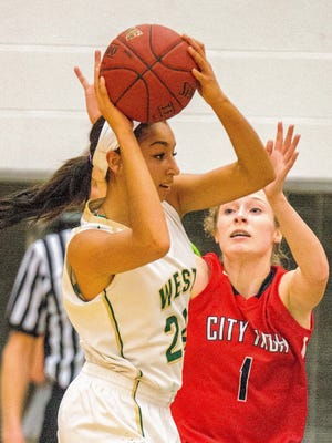Iowa City West's Mikaela Morgan (24) is guarded closely by Iowa City High's Sarah Plock (1) during the first half of play at Iowa City West High on Friday, February 13, 2015.