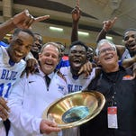 MTSU head coach Kermit Davis (center left) and his players celebrate the Great Alaska Shootout championship win on Nov. 28, 2015.