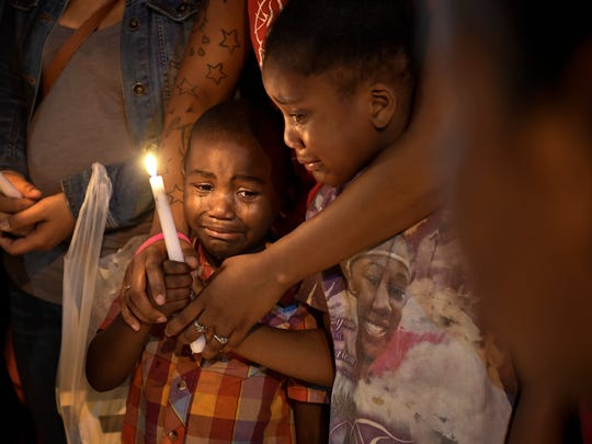 Latrelle Cox Jr. and Corionna Offutt are held by their mother as they pay their respects for Deberianah Begley during a candlelight vigil at the James Cayce Public Housing Development in Nashville, Tenn., Monday, Oct. 9, 2017.
