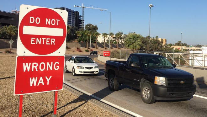 Vehicles come to a stop on the Seventh Street exit off Interstate 10 near downtown Phoenix. The Arizona Department of Transportation aims to prevent wrong-way drivers with signs like these that keep people from entering the wrong ramp.