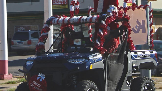 Bob Reynolds, a Salina resident, waves at the spectators lining the streets of the Salina Toy Run. Reynolds has played Santa in the run for 20 years.