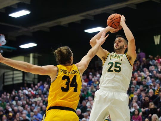 Vermont's Drew Urquhart (25) takes a shot over UMBC's Max Portmann (34) during the men's basketball game between the UMBC Retrievers and the Vermont Catamounts at Patrick Gym in January.