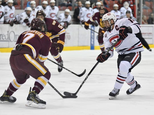 St. Cloud State's Judd Peterson (white) looks to shoot with Minnesota-Duluth's Scott Perunovich (7) defending on Friday at the Herb Brooks National Hockey Center.