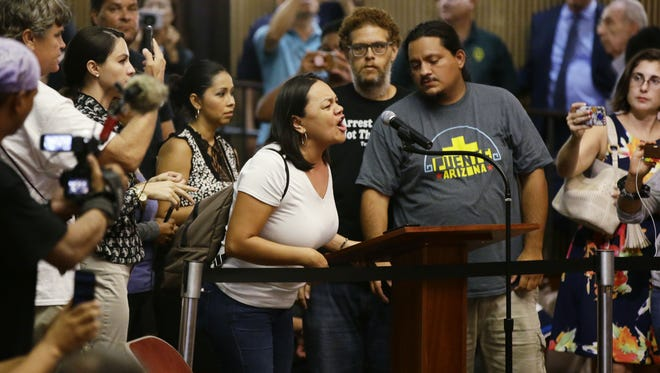Francisca Porchas of Phoenix tells her story of being teargassed by Phoenix police during the Aug. 22 Trump protest rally as Phoenix Mayor Greg Stanton walks out after calling a temporary adjournment for the Phoenix City Council meeting on Aug. 30, 2017.