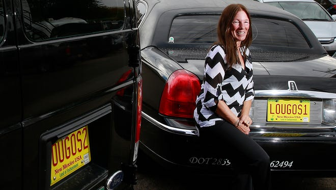 Kim Jones, transportation manager for Lou Go's, poses with two of the taxi service's vehicles, including a stretch limousine, on Sept. 21 at the business' office on 418 West Broadway Ave.