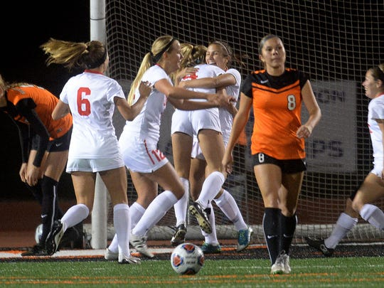 Rea Ritchie, far left, and Josselayne Pereda (8), right, of Ventura College, express disappointment as Santa Barbara's Chloe Montano (6) and her teammates celebrate a goal Tuesday night. The teams competed in the CCCAA Southern California regional semifinals at the VC Sportsplex.
