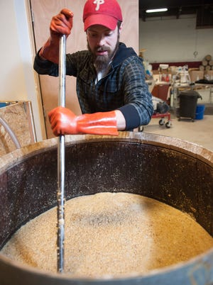 James Yoakum, owner of Cooper River Distillers in Camden, N.J., stirs whiskey mash. Yoakum has a craft license, which allows for production of up to 20,000 gallons annually.