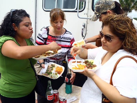 Women gather as they eat lunch from the Taco Bar Street