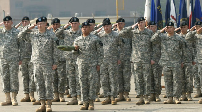 Soldiers of the U.S. Army 23rd chemical battalion salute during a ceremony April 4, 2013, in South Korea.