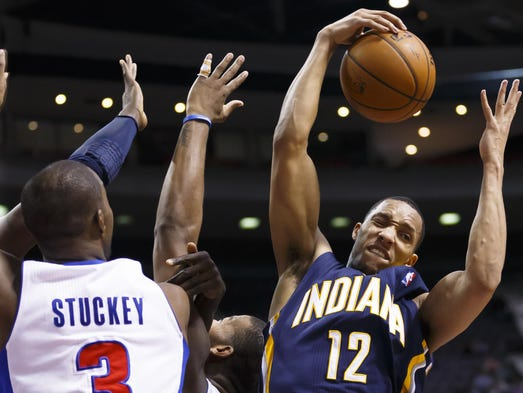 Indiana Pacers forward Evan Turner (12) grabs the rebound over Detroit Pistons guard Rodney Stuckey (3) in the fourth quarter at The Palace of Auburn Hills, Mich. Indiana won in overtime 112-104.