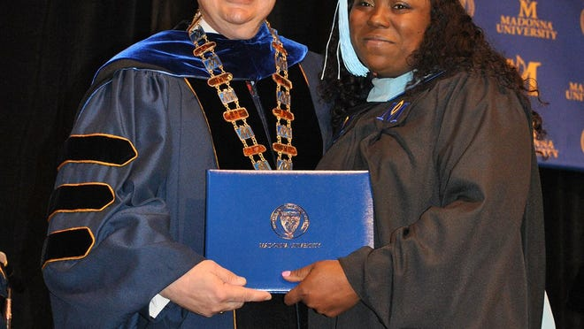 Madonna University President Michael A. Grandillo presents a master's degree in higher education and student affairs to Tanisha McIntosh of Westland in this file photo.