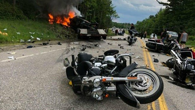 This photo provided by Miranda Thompson shows the scene where several motorcycles and a pickup truck collided on a rural, two-lane highway Friday, June 21, 2019 in Randolph, N.H.  New Hampshire State Police said a 2016 Dodge 2500 pickup truck collided with the riders on U.S. 2 Friday evening. The pickup truck was on fire when emergency crews arrived.