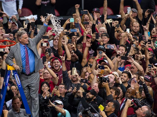 San Diego State coach Brian Dutcher shows off to fans the net he had just cut off, after the team's win 82-75 win over New Mexico in an NCAA college basketball game in the championship of the Mountain West Conference tournament Saturday, March 10, 2018, in Las Vegas. (AP Photo/L.E. Baskow)