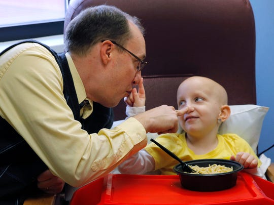 Paul Conrow plays with Amanda as they wait to be taken to a hospital room for an MRI at Strong Memorial Hospital.