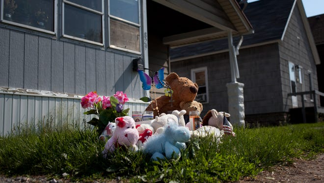 A memorial of candles, flowers and stuffed animals is seen Thursday in the front lawn of 829 Oak Street in Port Huron. A vigil will be held in memory of 5-year-old Mackenzie Maison at 8 p.m. Friday in the 800 block of Oak Street.