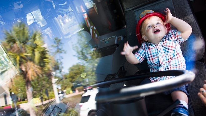 Everett Garcia, 19 months, looks up after putting a fire fighter hat on as he sits at the wheel in a fire truck on Saturday, April 8, 2017 at the inaugural Kidapalooza event at Golisano ChildrenÕs Museum of Naples. Families enjoyed face painting, a bike obstacle course, bounce houses and other hands-on activities.