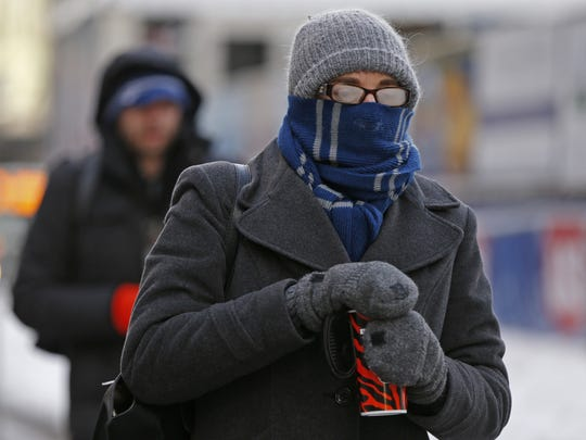 Monday, Jan. 27, 2014 COLDWEATHER METRO : Brianne Fahey of downtown walks the two blocks from her home to work in the extreme cold. The City is under an extreme wind advisory and it was -6 before sunrise.  The Enquirer/Jeff Swinger
