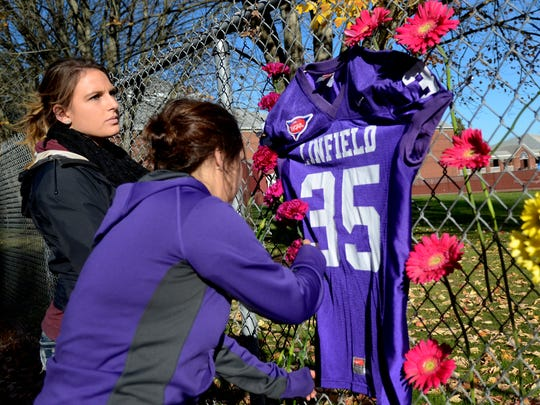 Anna Bruns, left, and Sydney Reynolds place flowers on a fence in memory of Parker Moore at Linfield College in McMinnville, Ore., on Sunday, Nov. 16, 2014. Moore, a sophomore business management major, was fatally stabbed Saturday night at a 7-Eleven next to the campus.