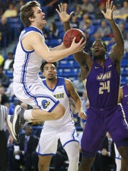 Delaware guard Ryan Daly (left) gets two points on a layup through traffic and James Madison's Dwight Wilson.