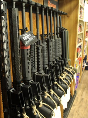 AR-15 guns sit on a rack at a store in this file photo.