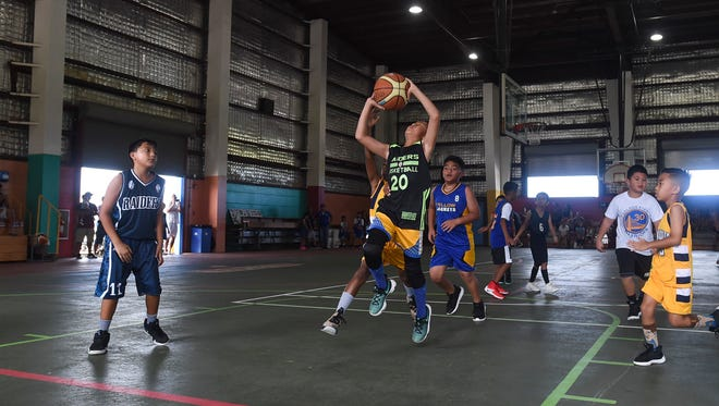 In this file photo, Raiders player Francis Jones (20) drives to the basket against the Yellow Jackets during a Guam Youth Basketball Association Drug Free League game at Astumbo Gym on June 9, 2018.