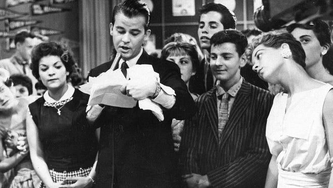 "Dick Clark is seen surrounded by fans during a television broadcast of ""American Bandstand."" Clark, the television host who helped bring rock `n' roll into the mainstream, died Wednesday, April 18, 2012 of a heart attack. He was 82."