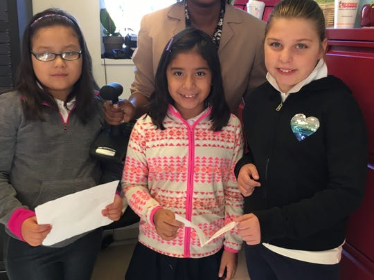 Shown standing in the foreground are from left to right Fabiana Salgado Pozo, Valentina Hernandez, and Julia Bosak, and Principal Perkins.