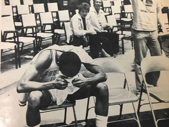 ASU forward Walt Stone sits alone on the ASU bench, head in hands, while Kansas fans cheer after KU defeated ASU in the NCAA tournament in March 1981.