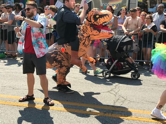 A dinosaur with ComedySportz had a message for the crowd during the Cadillac Barbie Pride Parade at Indy Pride Fest on June 9, 2018.