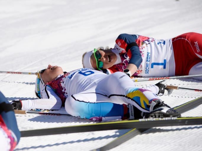 Charlotte Kalla of Sweden and Therese Johaug of Norway react at the finish line of theWomen's 7.5km + 7.5km Skiathlon competition in the Laura Cross Country Center at the Sochi 2014 Olympic Games.